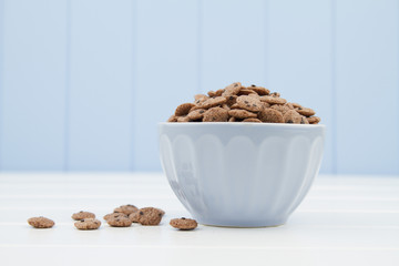 A blue bowl with cereals in the form of chocolate cookies