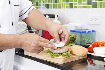 Chef putting onion hamburger on the bun