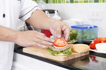 Chef putting slice of tomato on the Hamburger bun