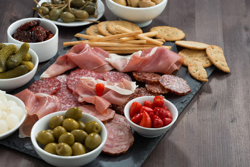 deli meat snacks, sausages and pickles on a dark wooden table