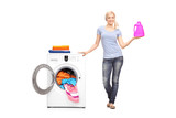 Woman holding detergent next to a washing machine