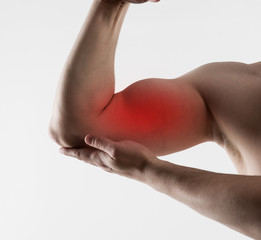 Muscle strain and stretch. Young man suffering from biceps pain
