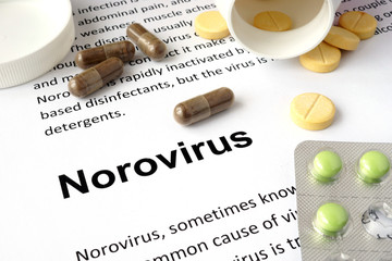 Paper with norovirus  and pills. Medical concept.