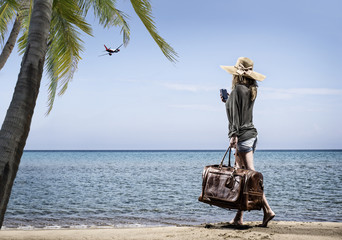 Woman on the beach with vintage leather bag