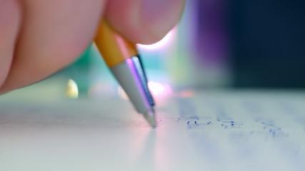 Pen writes a letter on paper