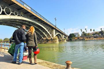 Couple of tourists on the bridge of Triana, Seville, Spain