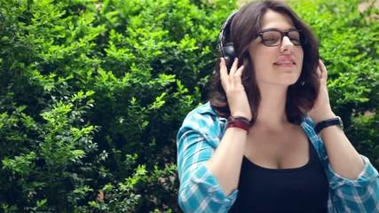 Woman wearing headphones listening to music and having fun