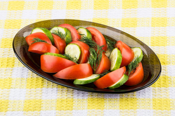 Salad of tomatoes and cucumbers with dill in dish on tablecloth