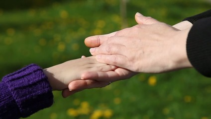 mom's hand gently stroking her daughter's hand
