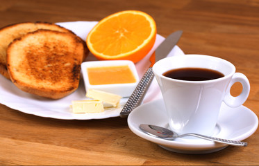 breakfast: cup of coffee, toasts, jam, butter and orange