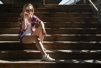Trendy hipster girl with sunglasses sitting on stairs