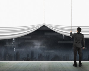 Man pulling open blank white curtain heavy rain dark cityscape