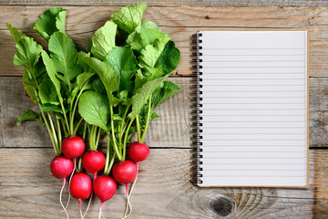 Fresh radish and recipe book on wooden background