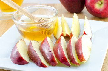 Apple with honey in plate on wooden table -Jewish New Year