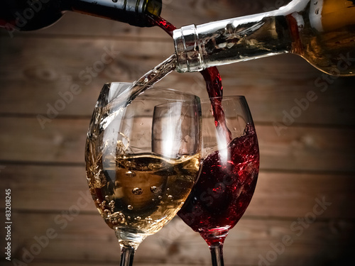 Red and wihite wine pour on wood background Poster