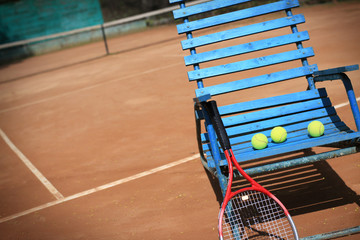 A tennis court and a blue wooden chair with balls