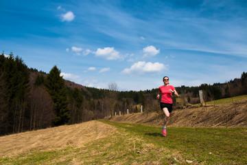 girl running the trail under blue sky