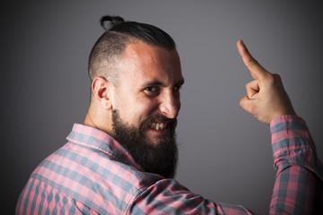 Joven con barba y camisa a cuadros haciendo cuernos