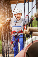 Happy boy on rope track in adrenalin park