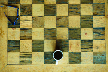 Part of chess old wooden table and coffee cup