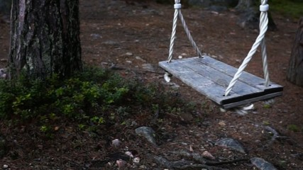 Empty vintage wooden swing moving gently