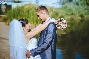 Married couple kissing on river beach. Bride Groom  couple