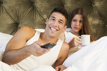 Man enjoying TV while his girlfriend is looking annoyed