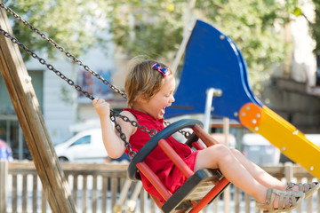 Laughing girl in red dres on chain swing