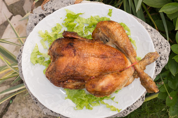 Whole roasted chicken with salad  on white plate