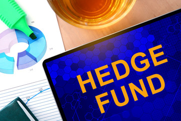 Words hedge fund  on the tablet and charts.