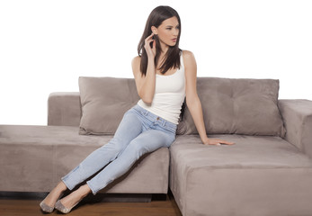 young woman in jeans posing on the couch