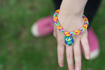 Girlie shows a rainbow rubber bracelet with owl.