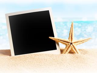 seashells and old photo frame on sand