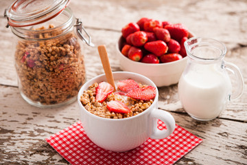 Healthy breakfast. Bowl of milk with granola and strawberries.