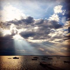Dramatic seascape at sunrise, sunrays shining through clouds