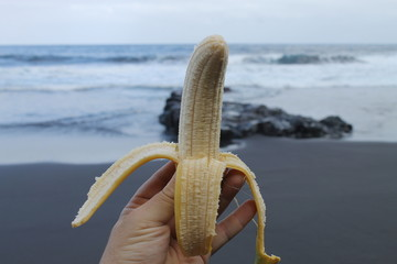 tomando plátano a la orilla del mar.