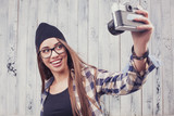 Hipster girl in glasses with vintage camera