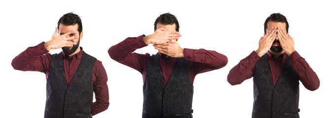 Man wearing waistcoat covering his eyes