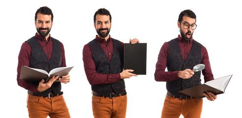 Man wearing waistcoat presenting book