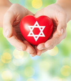 close up of hands holding heart with jewish star