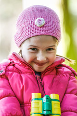 Little girl with binoculars in pink
