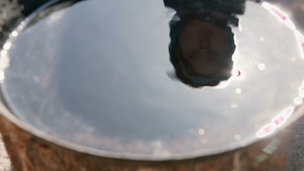 A silhouette of a little boy reflected in bowl of water