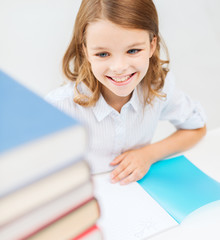 smiling little student girl with many books