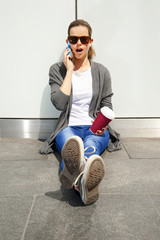 young woman leaning to wall in shock talking by phone in sunglas