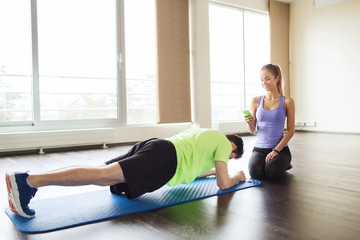 man and woman doing plank exercise on mat in gym