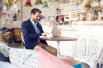 Young man using laptop at a cafe