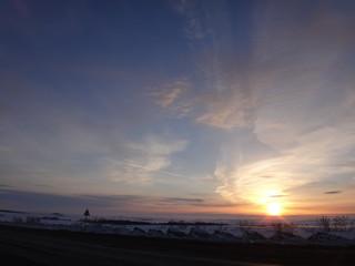 Бледно-желтый закат над зимним полем