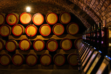 Wine barrels in the antique cellar. Cavernous wine cellar with