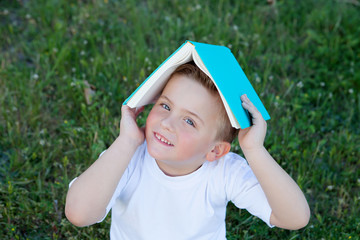 Little kid playing with a book at outside