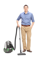 Young casual man posing with a vacuum cleaner